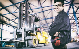 Smiling worker in protective uniform in front of forklift Royalty Free Stock Photo