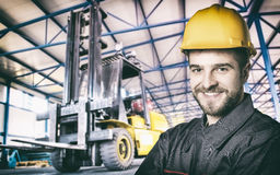 Smiling worker in protective uniform in front of forklift. Smiling worker in protective uniform in production hall in front of forklift - toned image, retro film Stock Images