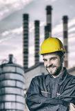 Smiling worker in protective uniform in front of industrial chim Royalty Free Stock Photo