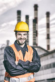 Smiling worker in protective uniform in front of industrial chim Stock Photos