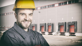 Smiling worker with protective uniform in front of shipping ware Stock Images