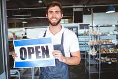 Smiling worker putting up open sign. At the bakery Royalty Free Stock Images