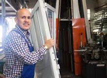Smiling worker at PVC windows factory. Portrait of smiling worker at PVC windows factory stock photography