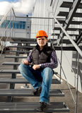 Smiling worker relaxing on metal staircase during break Stock Photos