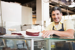 Smiling worker showing red velvet Royalty Free Stock Photos