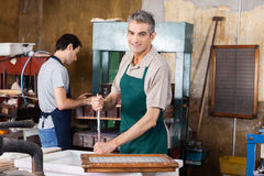 Smiling Worker Stirring Pulp And Water With Stick Royalty Free Stock Images
