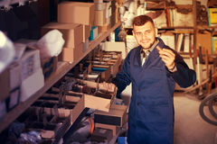 Smiling worker in uniform sorting sanitary engineering details Stock Images