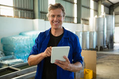 Smiling worker using digital tablet in factory royalty free stock photos
