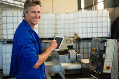 Smiling worker using digital tablet in factory royalty free stock photography