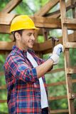 Smiling Worker Using Hammer In Wooden Cabin Royalty Free Stock Photography