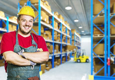 Smiling worker in warehouse. Smiling caucasian young manual worker in warehouse Royalty Free Stock Photography