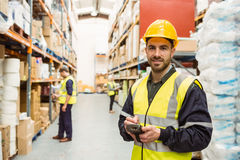 Smiling worker wearing yellow vest using handheld Stock Photo