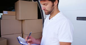 Smiling worker writing on pen. Front of delivery van stock video