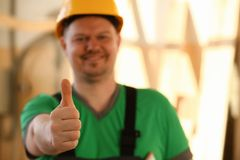 Smiling worker in yellow helmet show confirm sign. With thumb up at arm portrait. Manual job DIY inspiration joinery startup idea fix shop hard hat industrial royalty free stock photos