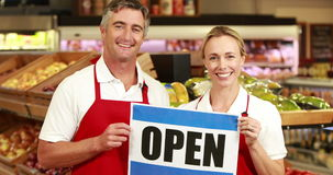 Smiling workers holding open sign stock video footage
