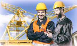 Smiling workers in protective uniforms in front of construction Stock Photos
