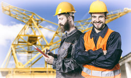 Smiling workers in protective uniforms in front of construction Royalty Free Stock Photography