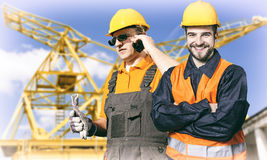 Smiling workers in protective uniforms in front of construction Royalty Free Stock Photos