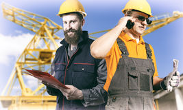 Smiling workers in protective uniforms in front of construction Stock Photo