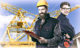 Smiling workers in protective uniforms in front of construction Stock Photography
