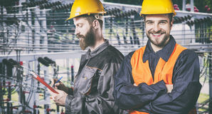 Smiling workers with protective uniforms in front of power plant Stock Photo