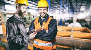 Smiling workers with protective uniforms in production hall Stock Image