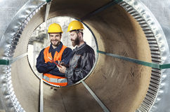 Smiling workers seen through a steel sheet metal roll Stock Image