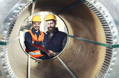 Smiling workers seen through a steel sheet metal roll Royalty Free Stock Image