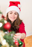 Smiling while working on the Christmas tree Royalty Free Stock Photos