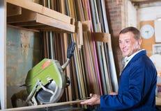 Smiling workman cutting wooden planks using circular saw. In workshop Stock Image