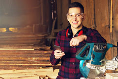 Smiling workman dressed in the checkered shirt and wearing protective glasses using his phone near the circular saw. royalty free stock image
