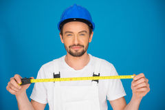 Smiling workman holding a tape measure Royalty Free Stock Photo
