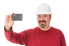 Smiling workman taking a self-portrait. Smiling workman with a goatee beard wearing a hardhat taking a self-portrait using his smartphone, isolated on white Stock Images