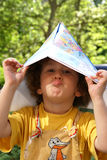 Smiling world. Curly boy with world map hat stock photography