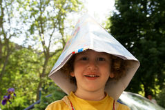 Smiling world. Little boy with paper cap royalty free stock images