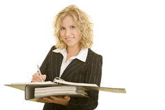 Smiling and writing. Young blonde woman making notes royalty free stock photography