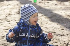 A smiling 2-year- old boy playing in a sandbox. Photo of a 2-year-old boy, wearing dark white-blue-black coverall, playing in a sandbox, happily smiling in early Stock Photo