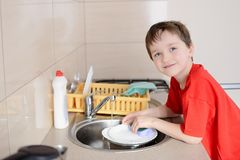 Smiling 7 year old boy washes dishes Royalty Free Stock Photo
