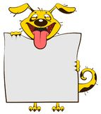 Smiling yellow dog holding blank white sheet of paper banner. Fun dog stick out tongue Royalty Free Stock Photography