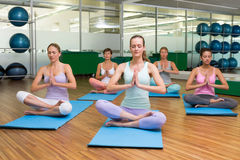 Smiling yoga class in lotus pose in fitness studio Stock Photo