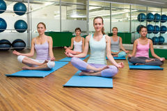 Smiling yoga class in lotus pose in fitness studio Royalty Free Stock Photo