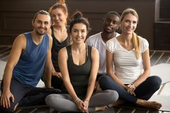 Yoga instructor posing with multiracial people at group training. Smiling yoga instructor teacher or pilates trainer coach looking at camera with multiracial royalty free stock photos