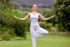 Smiling yoga woman standing on one leg in park Stock Images