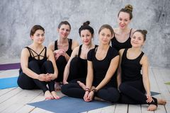 Smiling yogi girl exercising, having a break at class, group of friends watching on the phone stock photo