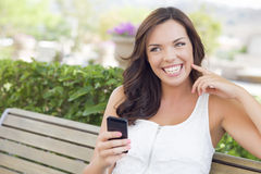 Smiling Young Adult Female Texting on Cell Phone Outdoors Royalty Free Stock Photography