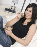 Smiling Young Adult Woman Eats Cereal With Fruit on Bed Royalty Free Stock Photos