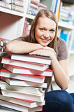 Smiling young adult woman reading  book in library Royalty Free Stock Image