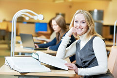 Smiling young adult woman reading  book in library Royalty Free Stock Images