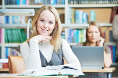 Smiling young adult woman reading  book in library Stock Images