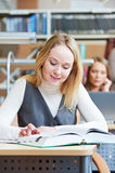 Smiling young adult woman reading  book in library Stock Photography